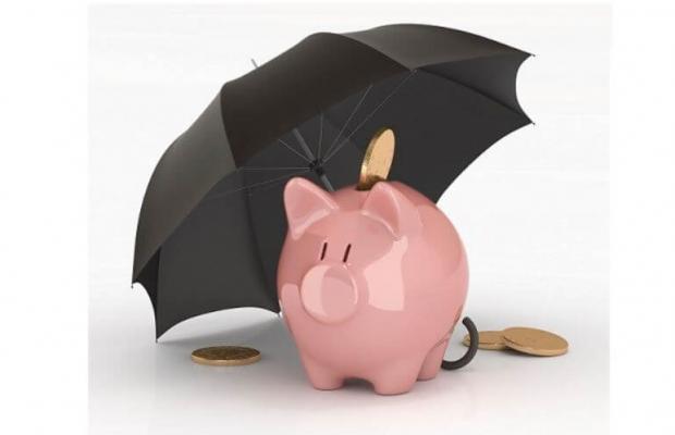 Bad Debt Protection with an umbrella over a piggy bank.